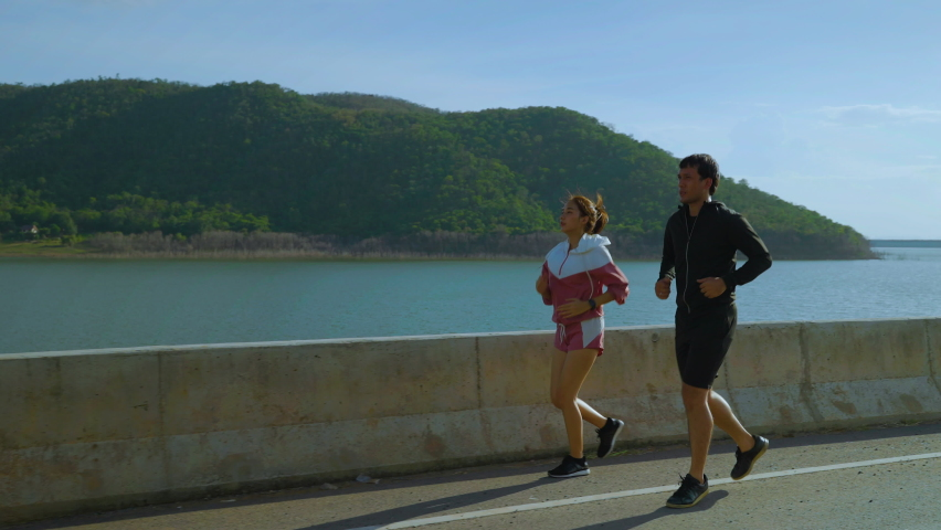 Couple jogging on the street, staying healthy concept   Shutterstock HD Video #1080825005