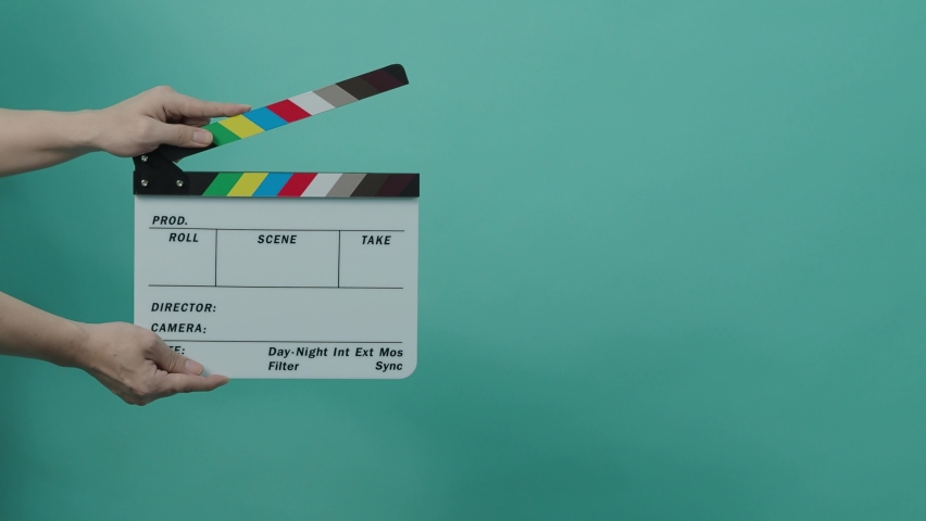 Clapperboard hitting. Movie film slate. close up hand clapping empty film slate on blue or green screen color background. in and out film slate cutting for video production. film or Movie shooting. | Shutterstock HD Video #1080832826