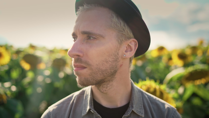 A young handsome serious Caucasian guy with dyed blond hair, piercing in light trousers, a gray shirt, a black hat in a sunflower field on a sunny day looks around and at the camera | Shutterstock HD Video #1080842456