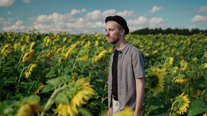 Young caucasian guy with dyed blond hair, pierced in light trousers, a gray shirt, a black hat walks in sunflower field on sunny day looks at the camera, looks back, takes a selfie on the phone camera | Shutterstock HD Video #1080842459
