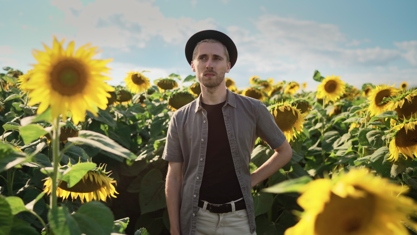Young handsome serious blond Caucasian guy with dyed blond hair, pierced in light trousers, gray shirt, black hat stands with his arms crossed in a sunflower field on a sunny day | Shutterstock HD Video #1080842468