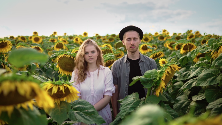 Young couple posing at the camera in a sunflower field on a sunny day: blond caucasian girl with curly hair in a light dress and a guy in a black hat look at the camera and turn away from each other | Shutterstock HD Video #1080842489