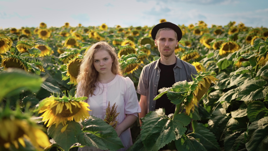 Young couple posing at the camera in a sunflower field on a sunny day: blond caucasian girl with curly hair in a light dress and a guy in a black hat look at the camera with a serious expression | Shutterstock HD Video #1080842492