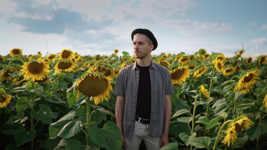 A young caucasian guy with dyed blond hair, pierced in light trousers, a gray shirt, a black hat in a sunflower field on a sunny day looks at the camera, looks back, takes a selfie on the phone camera | Shutterstock HD Video #1080842501