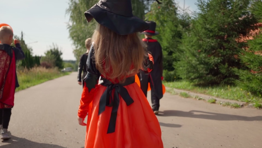 Halloween kids going to collect candy. Trick or treating. Guising. Jack o lantern. Children in carnival costumes outdoors. Witch and skeletons. Friends with orange balloons. celebrate halloween | Shutterstock HD Video #1080843917
