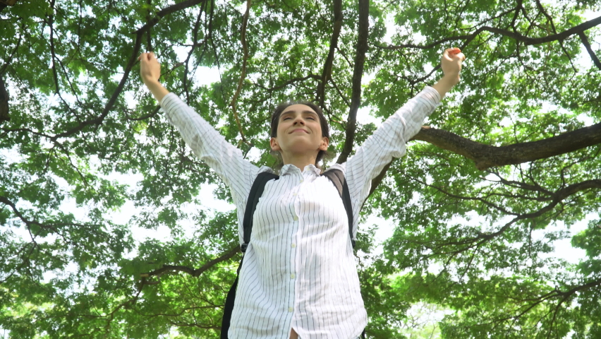 Happy young woman breathing deep fresh air closed eyes  and open arms enjoy calm in shade under spread branch of big tree    background . female smiling enjoy  nature in green forest . environment     Shutterstock HD Video #1080847349