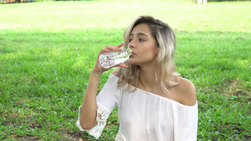 Happy young woman drinking water in shade under spread branch of big tree in park   Shutterstock HD Video #1080847376