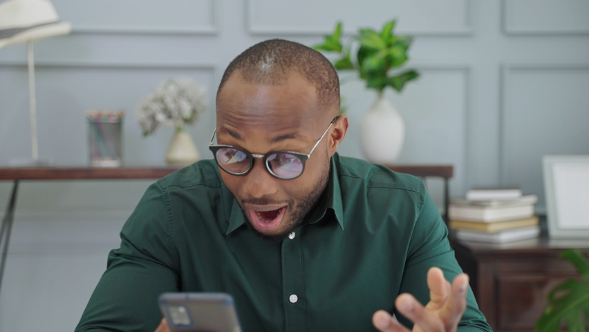African man Americans are wowed by the text messages they receive from their smartphones | Shutterstock HD Video #1080850577