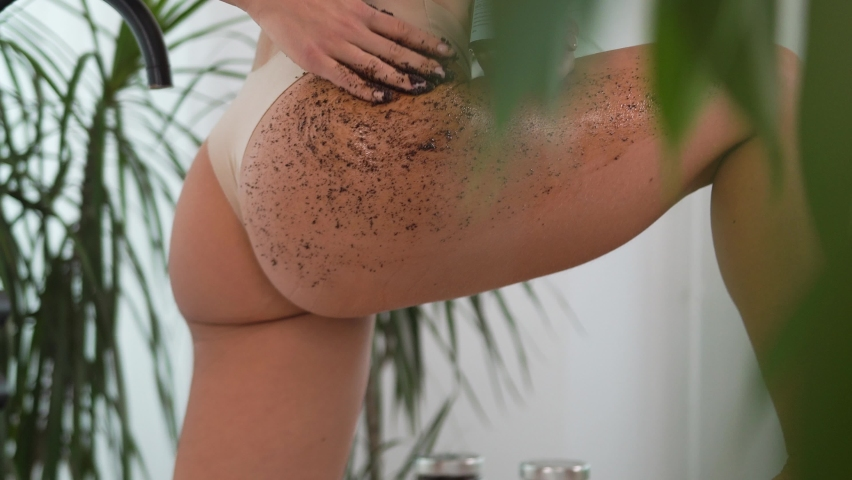 Woman smears body coffee scrub, runs hand over thigh, buttocks, massages skin, makes cleansing, peeling, skin care procedure makes smooth movements, removes dead cells cleansing care bath, among green | Shutterstock HD Video #1080856706