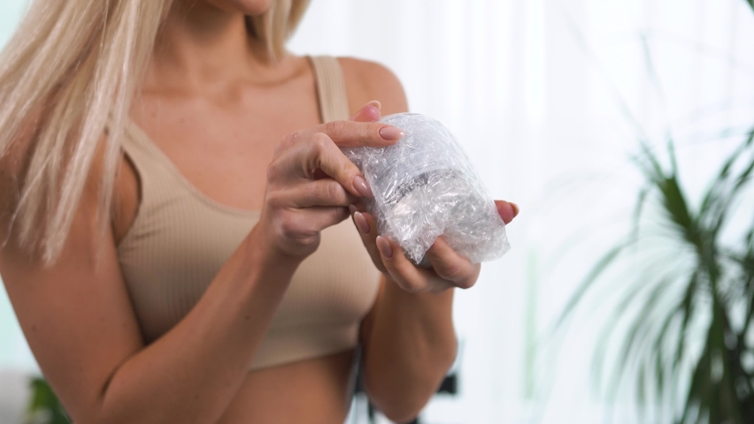 Twirls hand glass jar polyethylene soft airy package scrub, cream, tonic. Blonde underwear stands bathtub home near green foliage. High-quality, reliable home delivery. Taking care yourself, your body | Shutterstock HD Video #1080856709