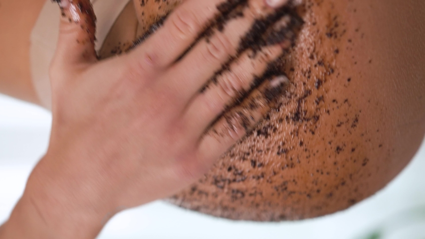 Close-up female smears her body with coffee scrub, runs hand over thigh, massages skin, makes cleansing, peeling, skin care procedure makes smooth movements, removes dead cells, salon, cleansing care | Shutterstock HD Video #1080856721