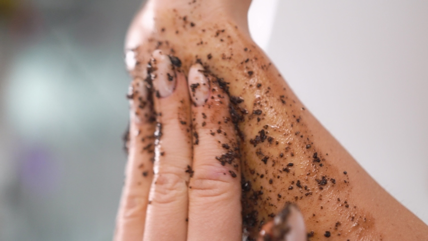 Close up female smears her body with a coffee scrub, runs over hand, massages skin, makes cleansing, peeling, skin care, procedure makes smooth movements, removes dead cells, salon, cleansing care  | Shutterstock HD Video #1080856724
