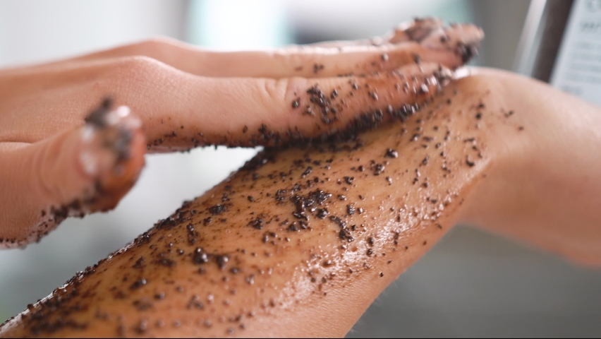 Close-up female smears her body with a coffee scrub, runs over hand, massages skin, makes cleansing, peeling, skin care, procedure makes smooth movements, removes dead cells, salon, cleansing care  | Shutterstock HD Video #1080856730