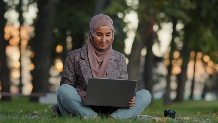 Happy smiling friendly islamic woman muslim girl in hijab sitting on grass lawn in park outdoors in city making video call online chat conference talking on webcam using laptop distant chatting app Royalty-Free Stock Footage #1080892874