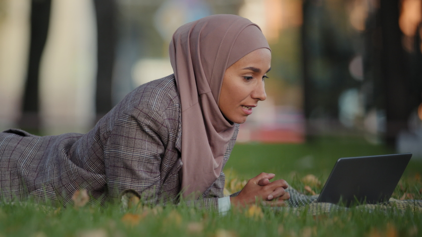 Friendly islamic business woman muslim girl in hijab lying grass lawn in park outdoors female teacher online mentor making video call chat conference talking webcam using laptop distant communication Royalty-Free Stock Footage #1080892883