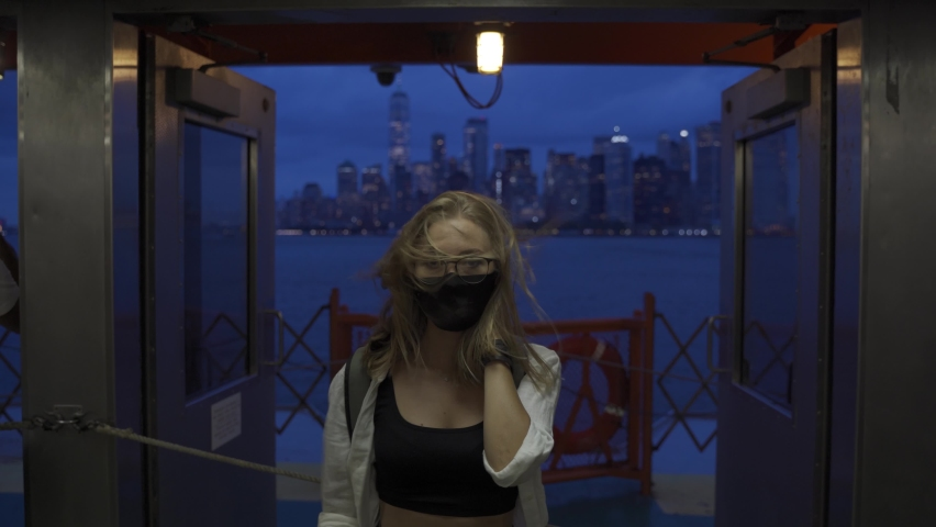 A female looks off into the distance, deep in thought while staring at the New York City skyline while riding the Staten Island Ferry. Back view of tourist on Staten Island Ferry approaching Manhattan   Shutterstock HD Video #1080899645