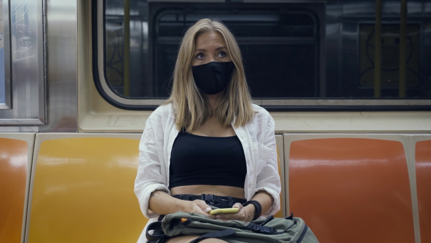 Portrait of a woman in a black medical face mask to avoid the spread of coronavirus who is sitting alone in a modern subway car. A girl in a surgical mask is keeping social distance on a metro train.   Shutterstock HD Video #1080899648