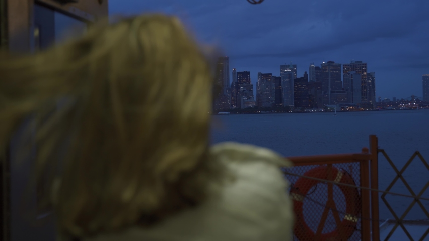 A female looks off into the distance, deep in thought while staring at the New York City skyline while riding the Staten Island Ferry. Back view of tourist on Staten Island Ferry approaching Manhattan   Shutterstock HD Video #1080899678