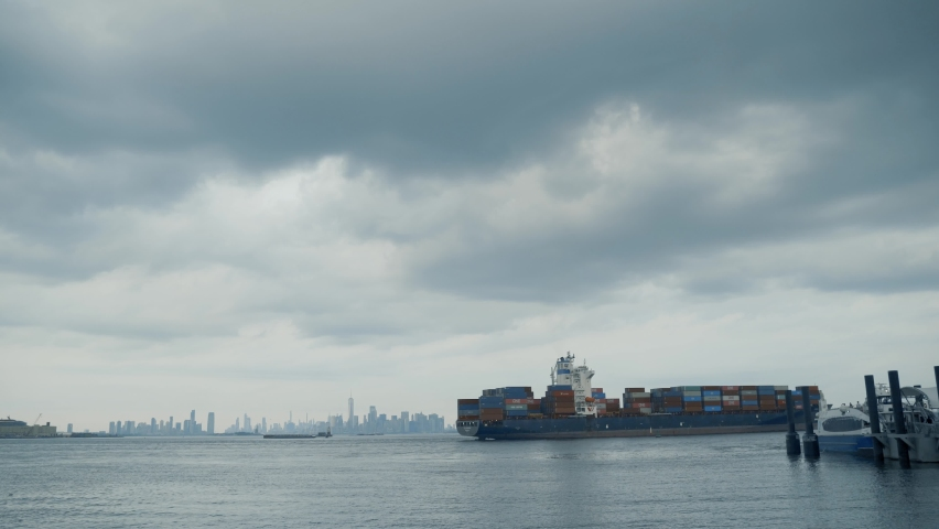 Container Ship floating along Hudson River against background with New York skyline in New York City, NY.   Shutterstock HD Video #1080950246