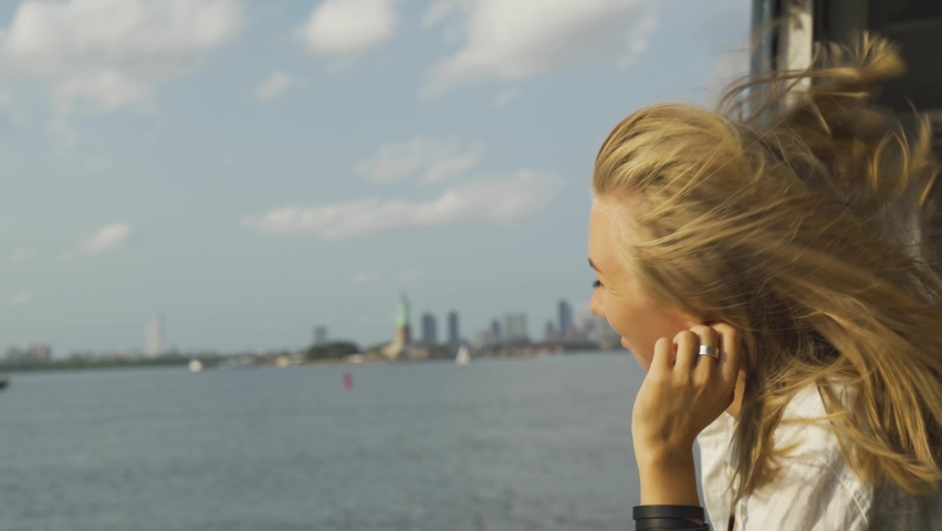 A young teenage girl takes in the view of lower Manhattan from a ferry. Blond woman watching liberty statue on background from the pier in the harbor. Travel, adventure, tourism concept.   Shutterstock HD Video #1080950258