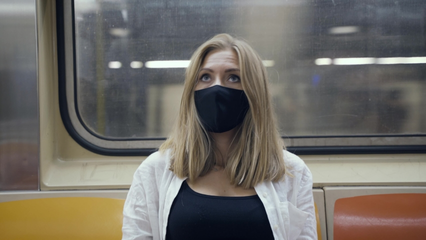 Portrait of a woman in a black medical face mask to avoid the spread of coronavirus who is sitting alone in a modern subway car. A girl in a surgical mask is keeping social distance on a metro train.   Shutterstock HD Video #1080950288