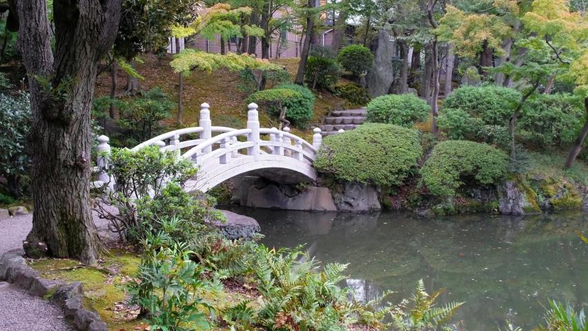 Video of white arch bridge over pond at the center of Former Yasuda Garden (Kyu-yasuda Teien), a small Japanese stroll garden located in Ryogoku. Tokyo. Japan | Shutterstock HD Video #1081012985