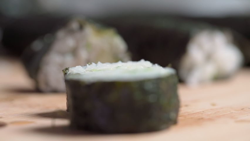 The chef lays down, sets for delivery pieces of sushi and roll made from seafood with Asian ingredients. Close up, macro. The background is blurred. Slow motion | Shutterstock HD Video #1081044227