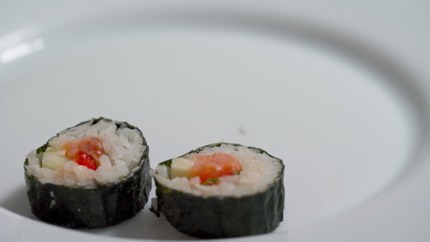 The chef lays down, sets for delivery pieces of sushi and roll made from seafood with Asian ingredients. Close up, macro. The background is blurred. | Shutterstock HD Video #1081046567