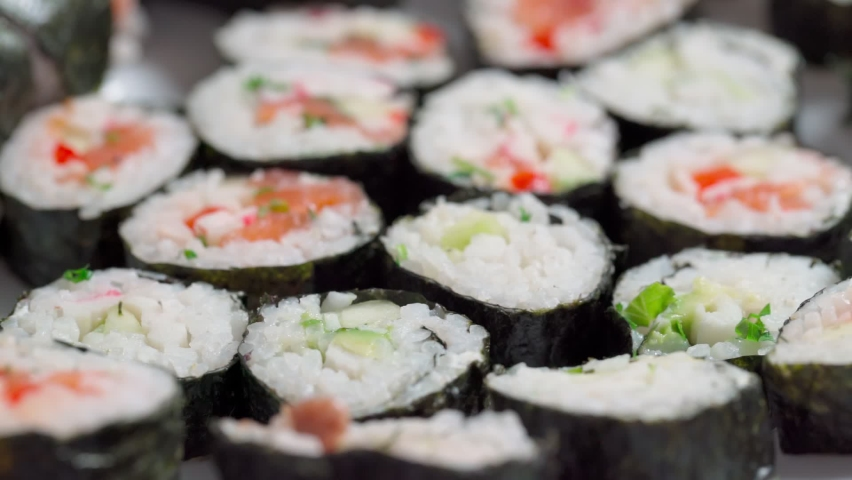 The chef lays down, sets for delivery pieces of sushi and roll made from seafood with Asian ingredients. Close up, macro. The background is blurred. Slow motion | Shutterstock HD Video #1081046579