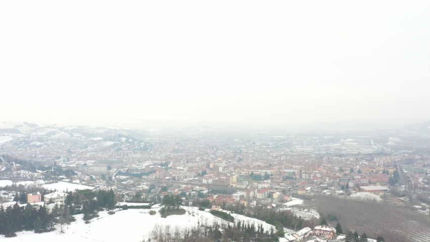 Panoramic aerial view of Alba, City in Italian Piedmont. Winter time, snow, fog. Drone. | Shutterstock HD Video #1081059362