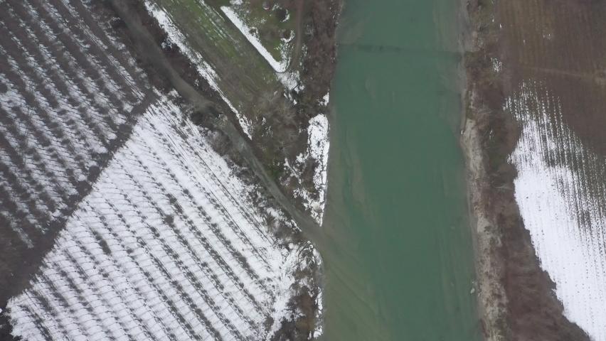 Zenith overhead view of Tanaro River near city of Alba in Italian Piedmont. Winter with snow, vineyards, green water. 4K | Shutterstock HD Video #1081059371