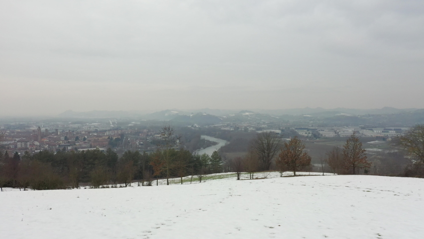 Drone rising up over a snowy hill showing city panoramic of Alba in Italian Piedmont region. Tanaro River, hills, cityscape, snow, vineyards, winter season. 4K | Shutterstock HD Video #1081059377