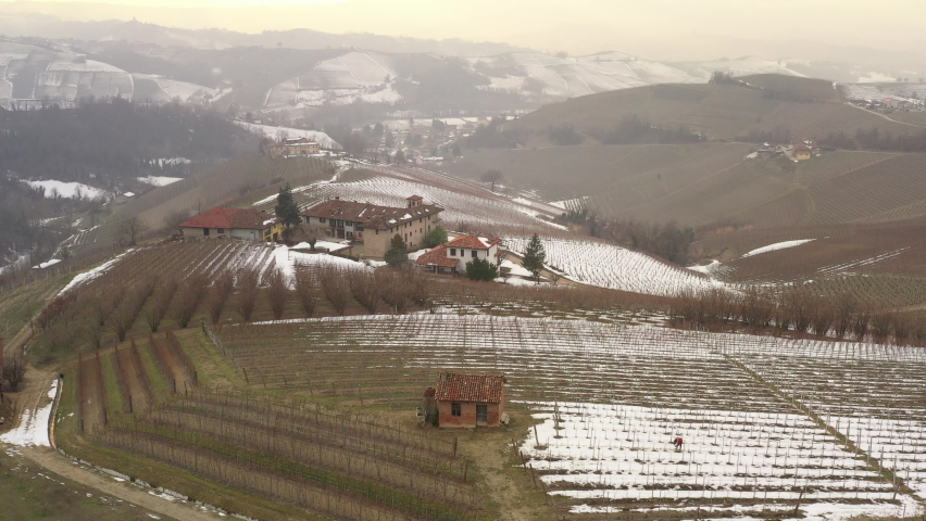 Drone flying over and approaching a farm with vineyards in Italian Piedmont region. A farmer working in sown, snow, winter season. Patterns, textures. 4K | Shutterstock HD Video #1081059392