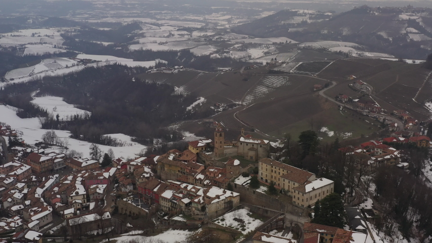 Aerial shot over Italian region Piedmont, in an ancient city - Alba - surrounded by hills, vineyards, roads, sown. Winter season, snow. Sunset, panoramic region view, drone descending, tower, church. | Shutterstock HD Video #1081059395