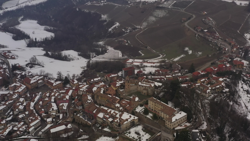 Aerial shot over Italian region Piedmont, in an ancient city - Alba - surrounded by hills, vineyards, roads, sown. Winter season, snow. Drone descending showing old facades, clock tower, church. 4K | Shutterstock HD Video #1081059401