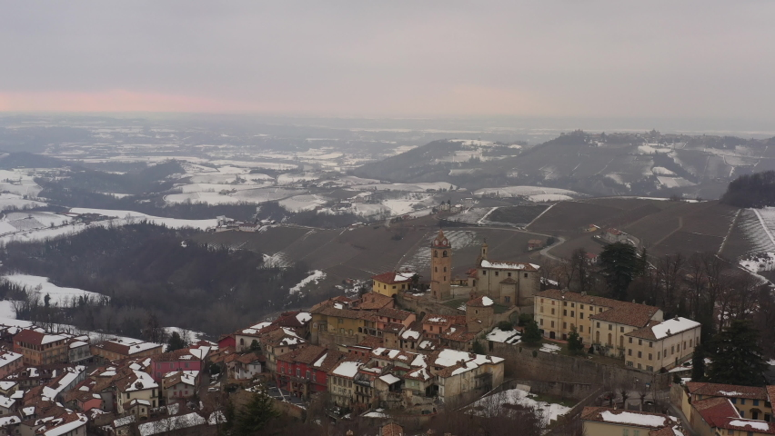 Aerial shot over Italian region Piedmont, in an ancient city - Alba - surrounded by hills, vineyards, roads, sown. Winter season, snow. Drone descending showing old facades, clock tower, church. 4K  | Shutterstock HD Video #1081059413