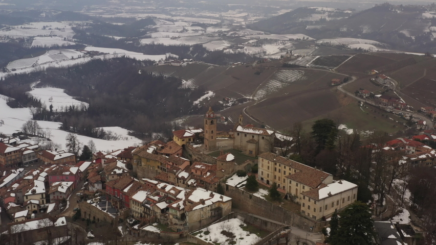 Aerial shot over an ancient city - Alba - in Italian region Piedmont,  surrounded by hills, vineyards, roads, sown. Winter season, snow. Clock tower, old facades, church. 4K | Shutterstock HD Video #1081059416