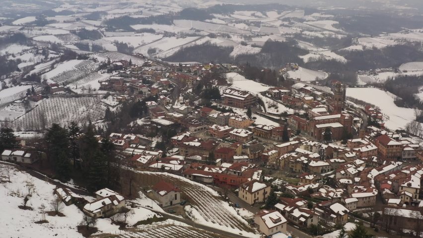 Aerial shot over Italian region Piedmont, in an ancient city - Alba - surrounded by hills, vineyards, roads, sown. Winter season, snow. Drone panning over the town showing old and new facades, church. | Shutterstock HD Video #1081059419