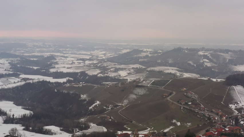 Aerial shot over Italian region Piedmont, in an ancient city - Alba - surrounded by hills, vineyards, roads, sown. Winter season, snow, sunset. Drone descending showing clock tower, old facades. 4K | Shutterstock HD Video #1081059425