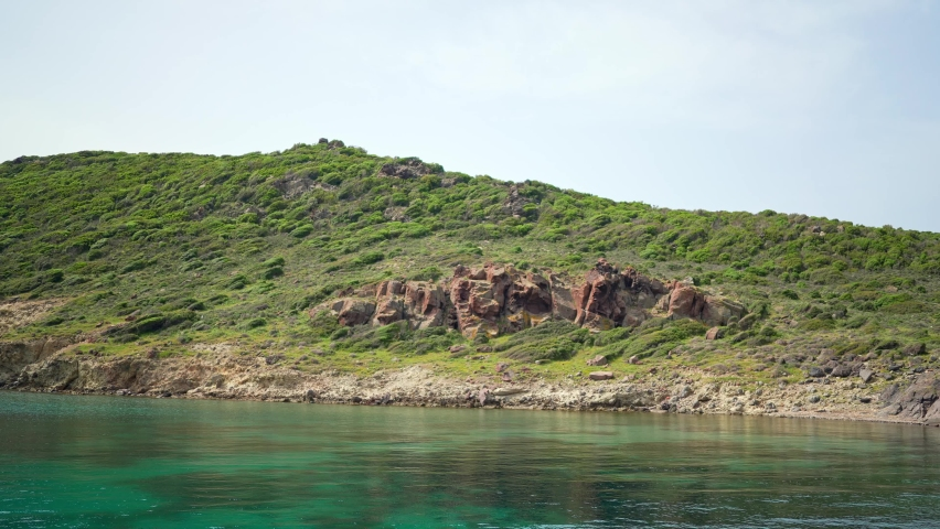Red rocks on the shore. The cliffs of a deserted island.   Shutterstock HD Video #1081060961