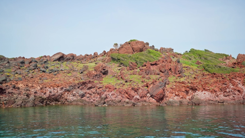 Red rocks on the seashore. The cliffs of a deserted island.   Shutterstock HD Video #1081060964