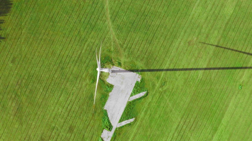 Large wind turbine and its long shadow in the green fields. Top aerial view  | Shutterstock HD Video #1081248104