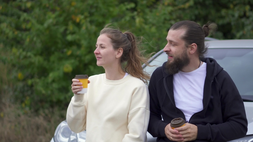 Together drink coffee on street and talk, Couple on picnic date by car. Real life laugh. Smile wind blows hair. Students in ordinary clothes. look away. disposable cups for coffee. Paper cups. | Shutterstock HD Video #1081254140