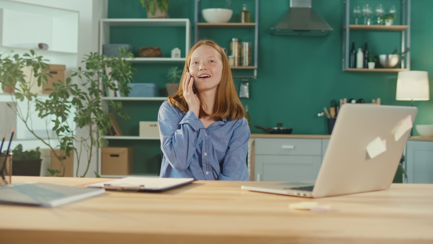 Red Haired Teenage Girl Studying Online, Chatting on a Cell Phone, Spinning on the Chair at Home. Modern Technologies and Communications. Teenagers' Communication Concept. Mental Health. | Shutterstock HD Video #1081268222