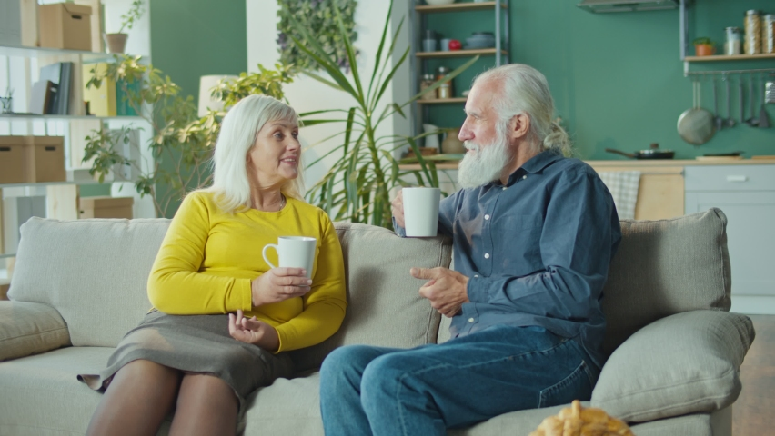The Affectionate Elderly Couple is Relaxing on the Couch Enjoying a Pleasant Conversation While Holding Cups of Hot Tea. Happy Elderly Couple Relaxing at Home. Seniors Happy Lifestyle Concept. | Shutterstock HD Video #1081268405