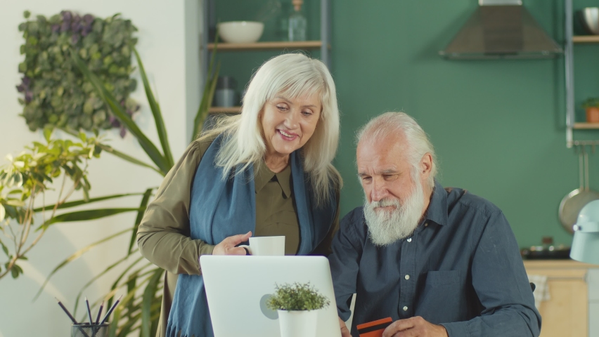 Excited happy elderly couple in Santa Claus hats are choosing Christmas gifts and shopping online using laptop and credit card at home. Holiday shopping and online shopping concept. | Shutterstock HD Video #1081268414