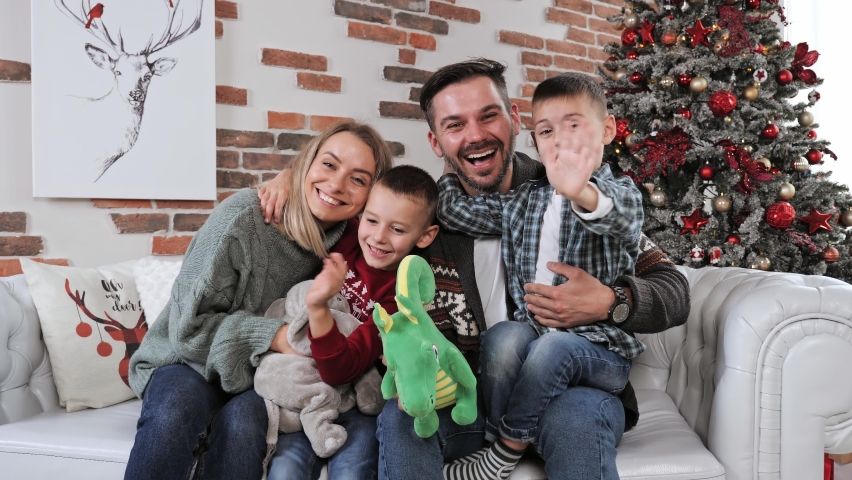 Cheerful happy married couple with two children waving hands laughing having fun at home for Christmas posing to camera indoor modern technology New Year 2022 congratulations to family or friends. | Shutterstock HD Video #1081274669