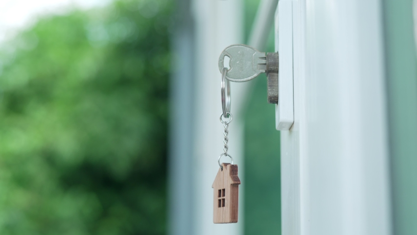 Deal contract complete. Sell your house, rent house and buy ideas. The house key for unlocking a new house is plugged into the door.The keychain is blowing in the wind. | Shutterstock HD Video #1081280171