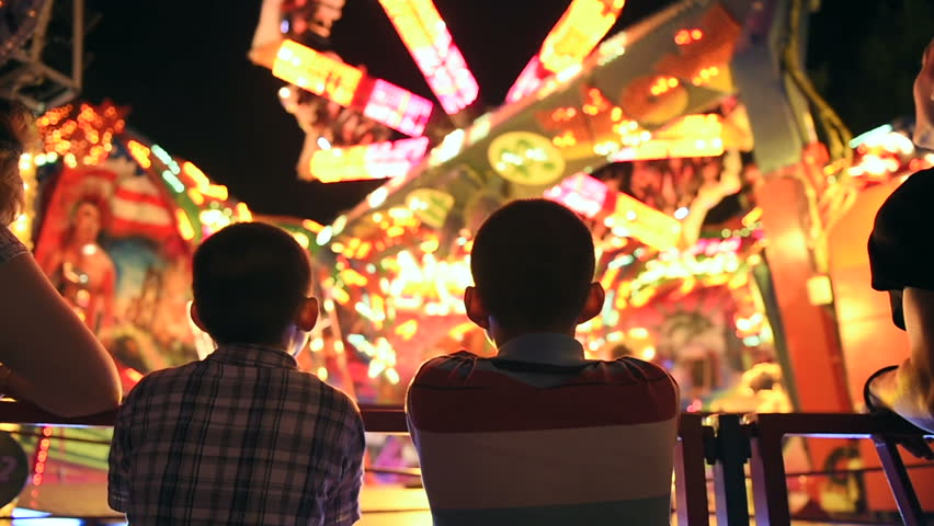 Two young brothers next to their mother admiring the spinning carousel at night, at amusement park in France - slow motion | Shutterstock HD Video #10827731