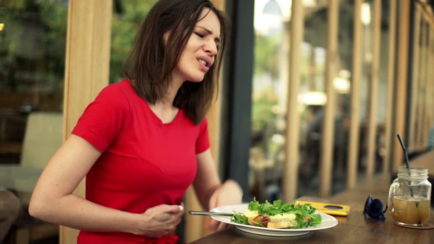 Young woman gets stomach ache during meal in cafe